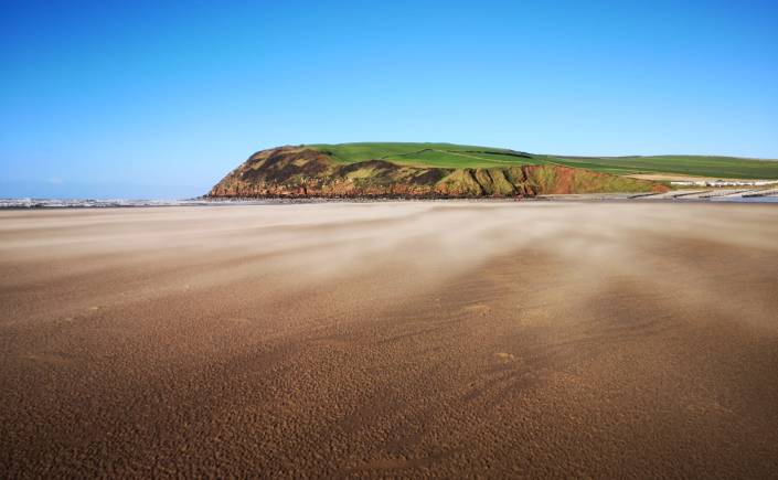 Blue skies over head and sand blowing across the beach at St Bees